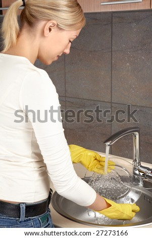 The blonde washes ware at a bowl on kitchen