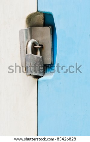 The blue door is locked with a old padlock. - stock photo