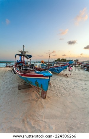 The blue fishing boat on white sand during a sunset. - stock photo