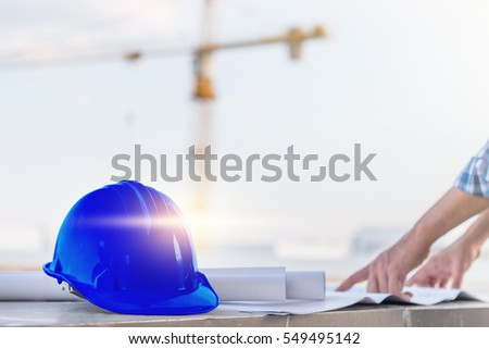 The blue safety helmet with the man verify blueprint for his project