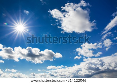 The blue sky with clouds and sun beams - stock photo