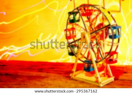 The blurry photo of ferris wheel toy model with multicolor light at the back on lomography style represent the toy and amusement background concept related idea.