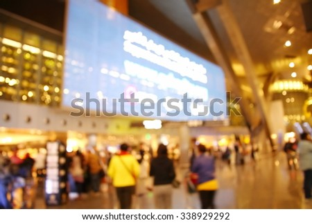 The blurry scene of terminal hall in the scene appear the big led screen among the colorful light decoration in the hall represent the travel industry concept airport atmosphere concept related idea. - stock photo