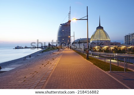 The boardwalk along the river Weser at Bremerhaven (Germany, federal state Bremen) taken in the evening at the blue hour. - stock photo