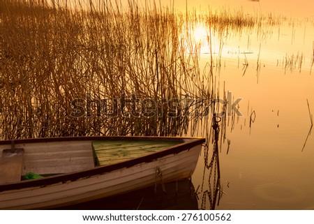 The boat docked on the lake Balaton at sunset - stock photo