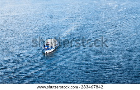 The boat floating in the blue Dnieper waters.