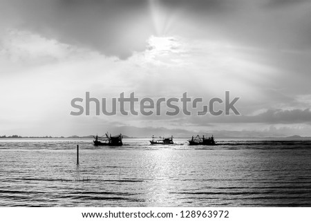 The Boat under the sunset silhouette on the sea