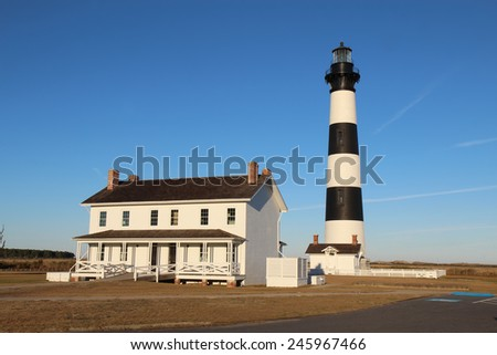 The Bodie Island lighthouse and keeper's quarters at the Cape Hatteras National Seashore against a bright blue sky - stock photo