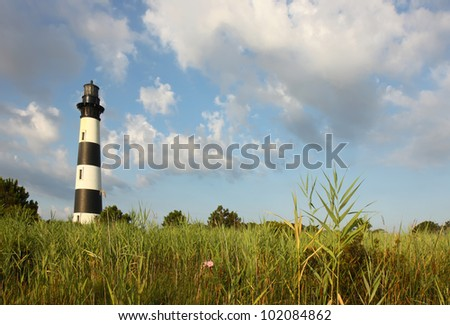 The Bodie Island lighthouse over marshes of the Cape Hatteras National Seashore on the Outer Banks of North Carolina against white clouds and a blue morning sky - stock photo