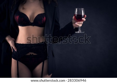 The body of a woman in sexy lingerie with glass of red wine in hand.