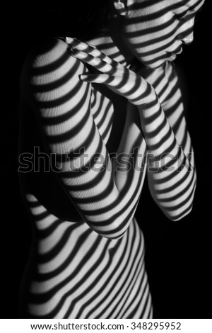 The body of nude woman  with black and white zebra stripes.  Black-and-white photo created with the projector - stock photo