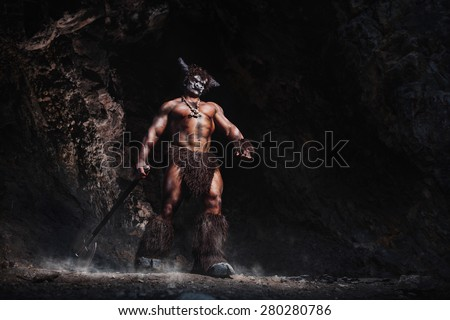The bodyart man angry minotaur with axe in cave - stock photo