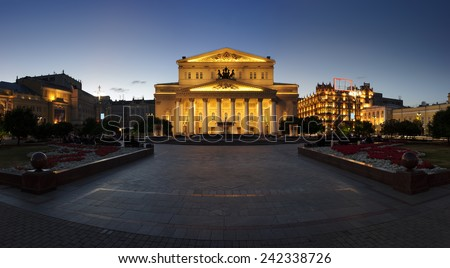 The Bolshoi Theatre near illuminated buildings, square with fountains, trees and flowers. Evening summer panorama. - stock photo