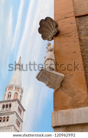 The Bonissima is medieval statue on the corner of the Town Hall and Torre della Ghirlandina in Modena, Italy - stock photo