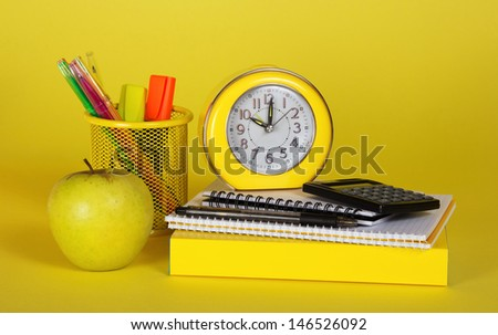 The book, accessories to the letter, the calculator an alarm clock and apple on a yellow background - stock photo