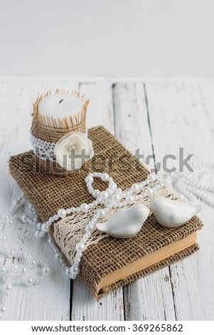 The book is in rustic style on a white table with a candle and a pearl necklace