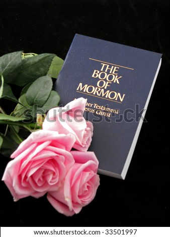 the book of Mormon and three pink roses on black background - stock photo