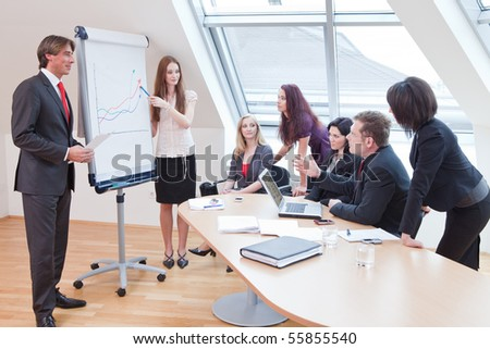 the boss is showing the new statistics on the flipchart - stock photo