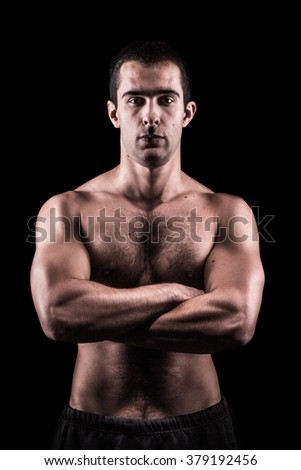 The bouncer, portrait of tough looking muscular young man, arms folded. - stock photo