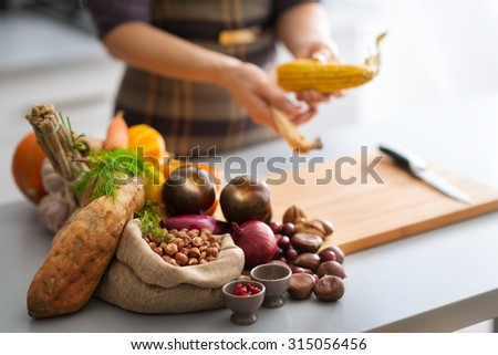 The bounty of the Autumn abounds in this photo, with sweet potato, nuts, cranberries, garlic, corn, red onions, and mini pumpkins on the menu for a delicious dish... - stock photo