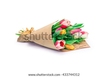 the bouquet of tulips is wrapped in a paper isolated on a white background - stock photo
