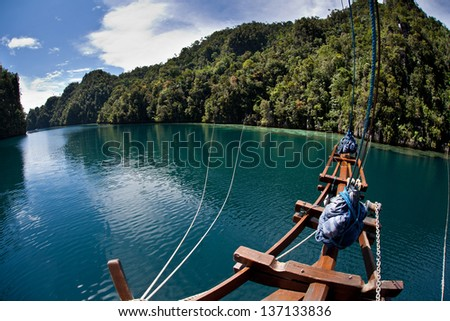 The bow of a sailing vessel is tied to limestone islands to secure it in a tight bay in Raja Ampat, Indonesia.