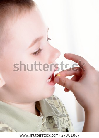 The boy accepts a tablet of vitamin