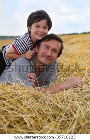 The boy and father on golden hay - stock photo