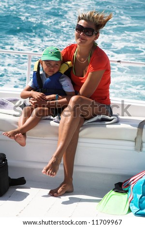 The boy and mum I go for a drive on a boat on the dark blue sea - stock photo