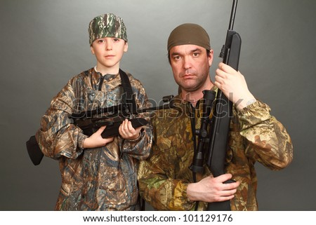 the boy and the adult man in a camouflage with rifles nearby in a shot, look in the chamber