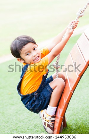The boy climbing the rope on the playground - stock photo
