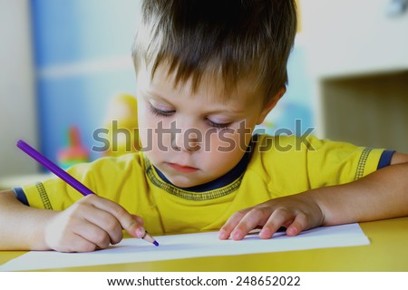 The boy draws a pencil at the table covered with a white tablecloth  - stock photo