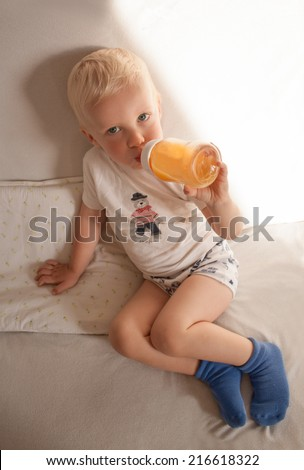 The boy drinking juice from a bottle - stock photo