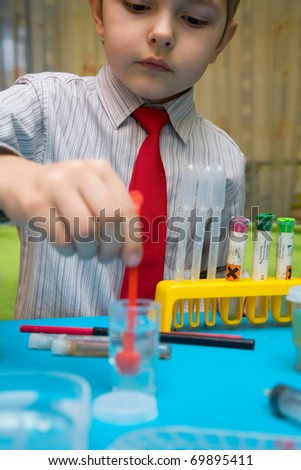 The boy enthusiastically studying chemistry and makes his first experience in chemical