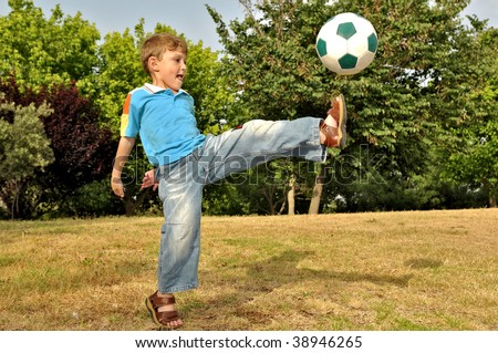 The boy from all force kicks the ball with his foot - stock photo