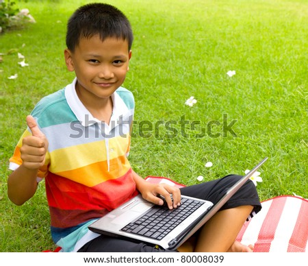 The boy happy with notebook on green grass at backyard - stock photo