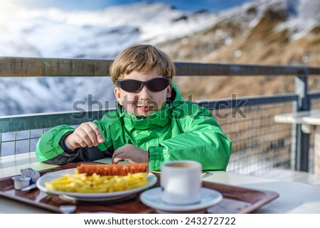the boy has dinner at mountain restaurant - stock photo