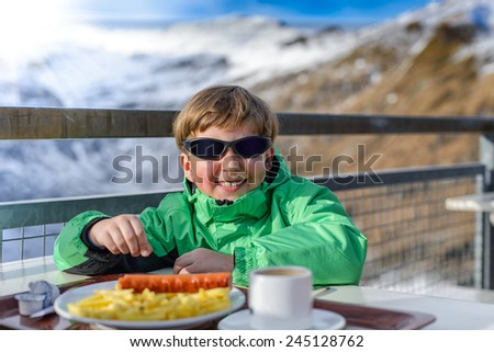 the boy has dinner at mountain restaurant - stock photo