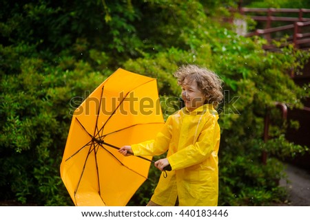 The boy holds an umbrella in hand, but doesn't hide under him from a rain. He likes to be under a warm summer rain. Child joyfully smiles. Behind him magnificent wet bush. - stock photo