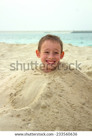 The boy in a heap of sand - stock photo