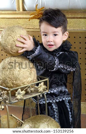 The boy in a suit of black prince raises the golden ball
