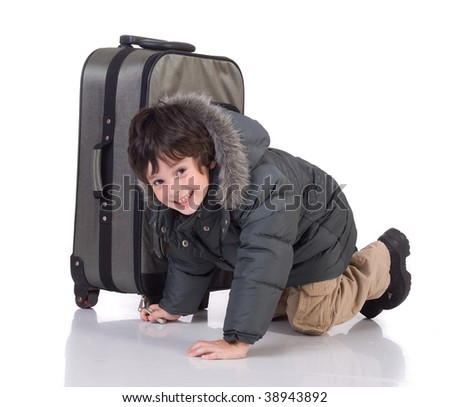The boy in gray winter jacket with  big suitcase - stock photo