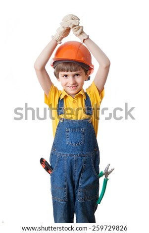 the boy in overalls and a helmet with hands above head - stock photo