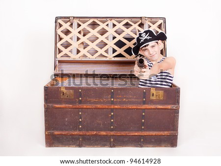 The boy in the image of a pirate, climbs out of the chest with treasures. a studio shot - stock photo