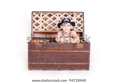 The boy in the image of a pirate, climbs out of the chest with treasures, a studio shot - stock photo