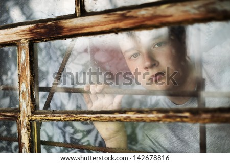 The boy it is sad looks out of the window through a lattice - stock photo