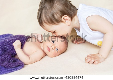 The boy kisses his newborn sister, girl, brother, kiss, love - stock photo