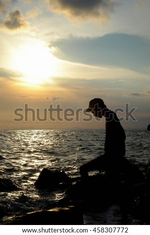the boy Man desperate He was standing by the sea, the light splash out