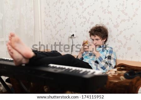 The boy plays phone, having put feet on the piano - stock photo