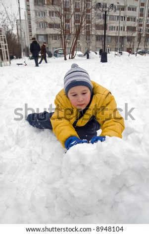 The boy rolls snow whom in winter day - stock photo